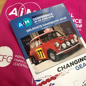 a pink bag and magazine with AIM conference logos
